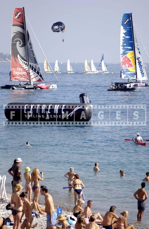 People watching race near Promenade des Anglais, colorful sailing photos.