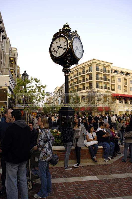 People sitting and Conversing near the Clock Post