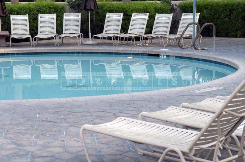 The Clear Blue Pool Reflecting the White Lounge Chairs