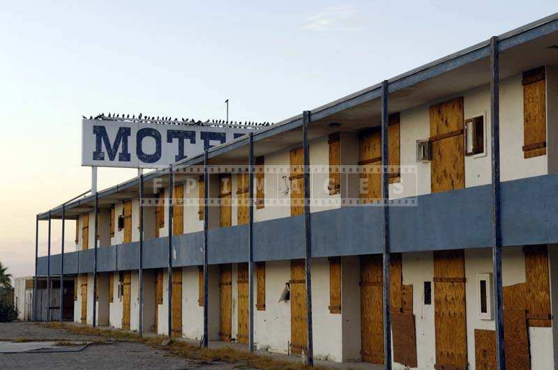 Boarded up motel doors and windows