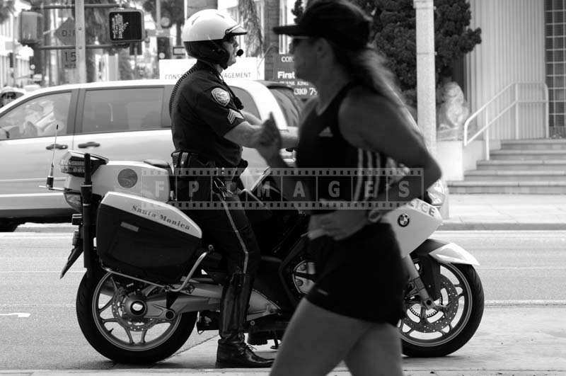 A Policeman Patrolling on a Bike as a Jogger Strolls on