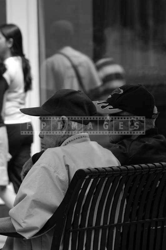 Two Men Wearing a Sports Cap Sitting on a Bench