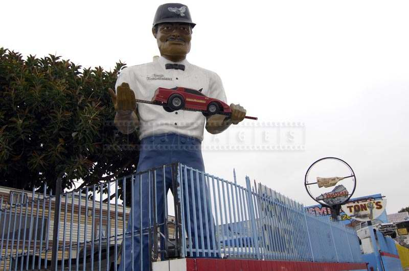 Tony The Muffler Man Holding a Car