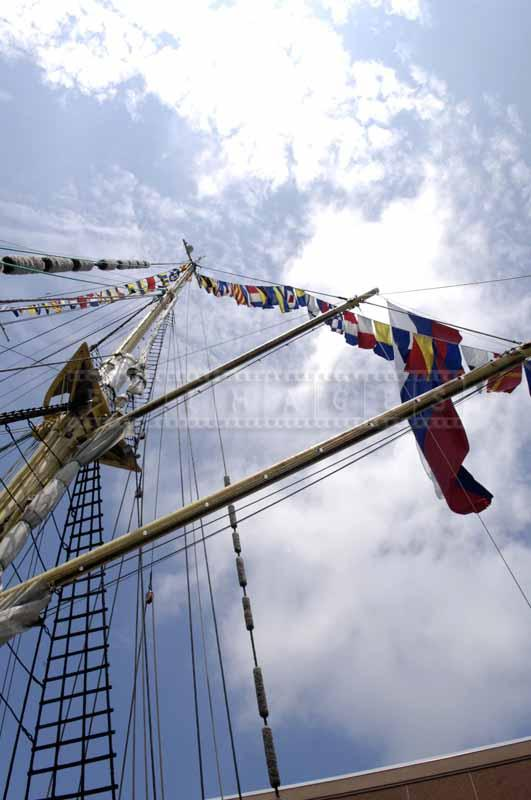 Looking up at the tall mast decorated with flags
