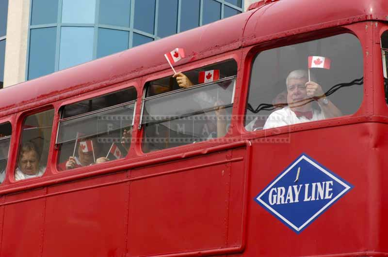 People with Canadian flags in double Decker bus