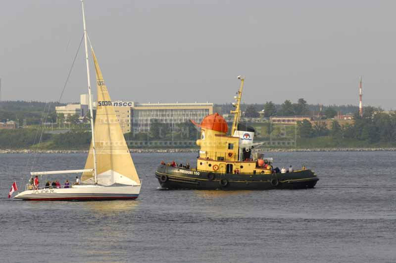 Theodore tug boat and a yacht in the harbor