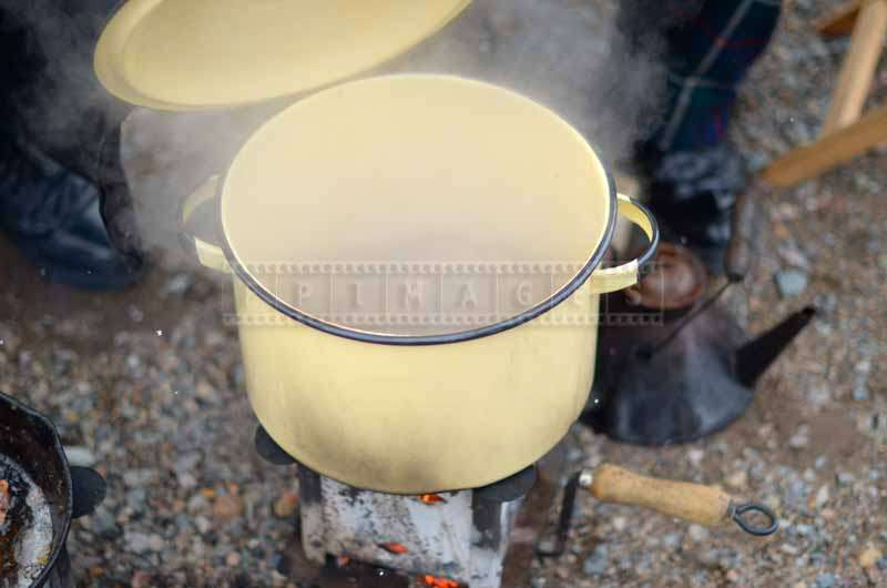 Camp cooker with a steaming pot