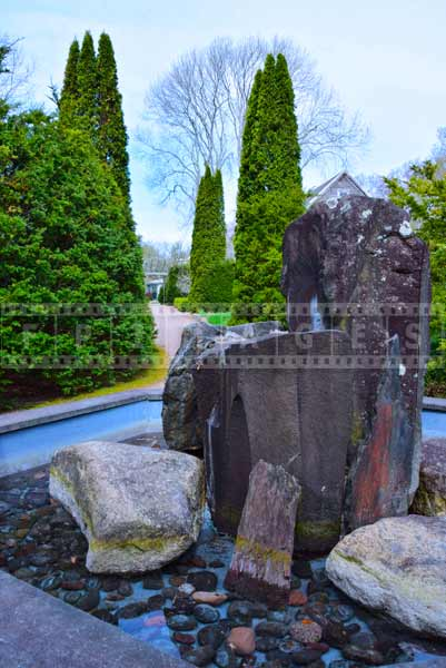 Nova Scotia rocks used to create rock fountain, cypress trees image