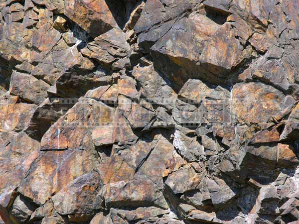 Rock texture formed by numerous polygons, strong lines, shapes and shadows