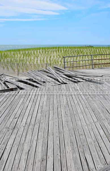 atlantic city boardwalk in need of repair and sand dunes protected with young vegetation