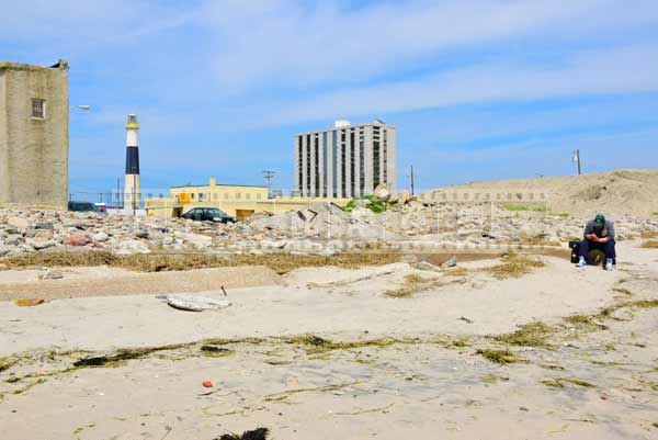 Absecon lighthouse and a man sitting on the shore littered with broken pieces of buildings