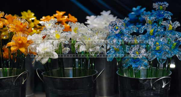 Orange, white and blue glass flowers for sale at the glass market, travel images