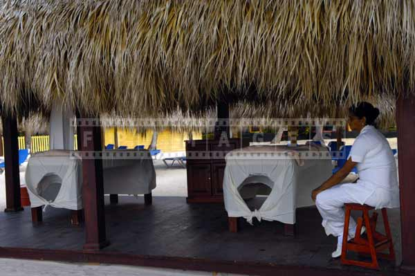 Palapa shelter with thatched roof used as a beachfront massage parlor