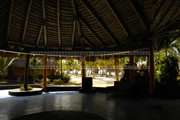 Large gazebo with a thatched roof dome providing shelter from tropical sun, architectural photography