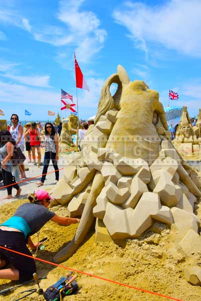 People looking at Canadian sand sculptor Melineige Beauregard