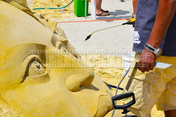 Spraying mist of water on sand sculpture