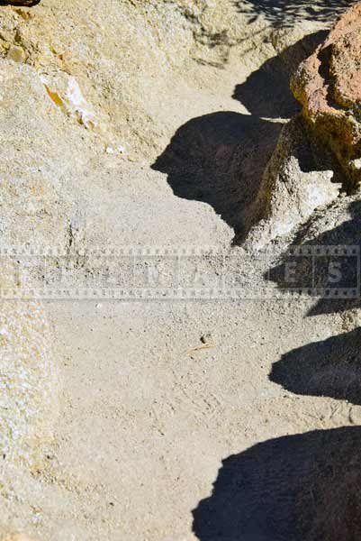 Sand and small rocks cover the trail, hiking trail detail photo
