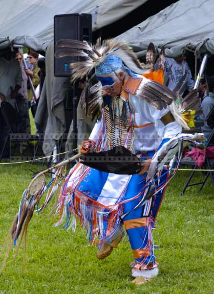 Photo of head dancer doing elaborate fancy dance movements and amazing regalia