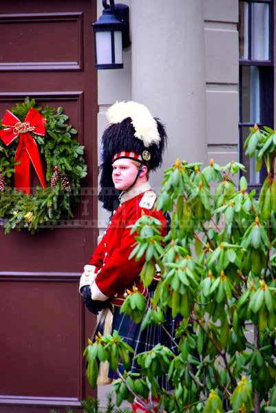 Guard in bright red highlander uniform with bearskin cap