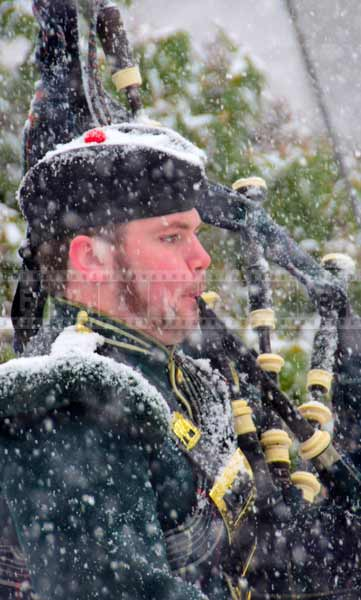 Close up portrait of a bagpipe player in heavy snow