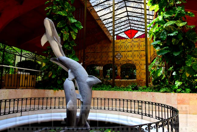 Dolphin sculpture and wrought iron decorations at hotel entrance
