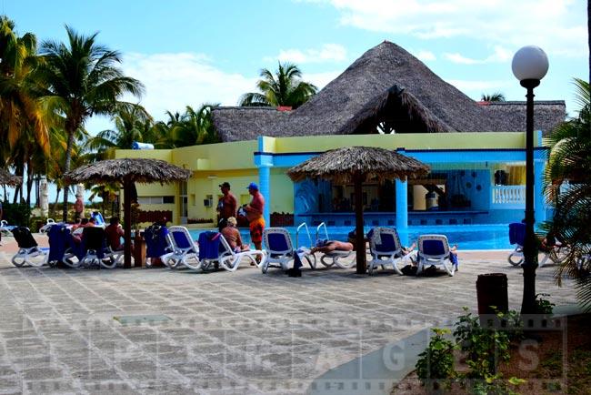 People enjoying sun and drinks near the pool