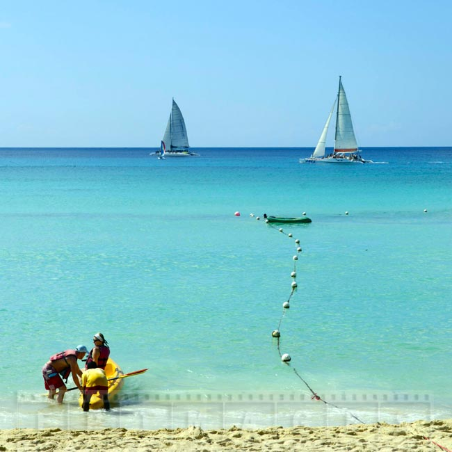 Couple preparing to paddle kayak at the beach