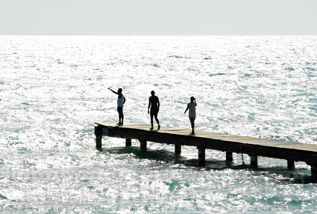 Three people at the wooden pier near the beach