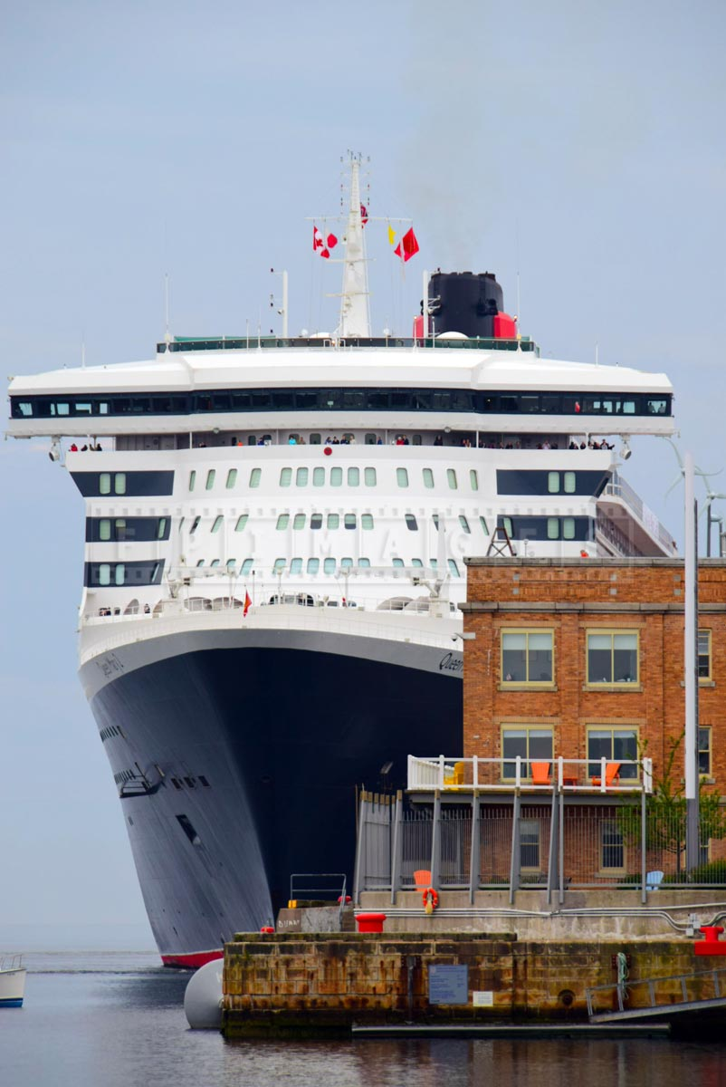 Large cruise ship Queen Mary 2 dominates the seaport buildings