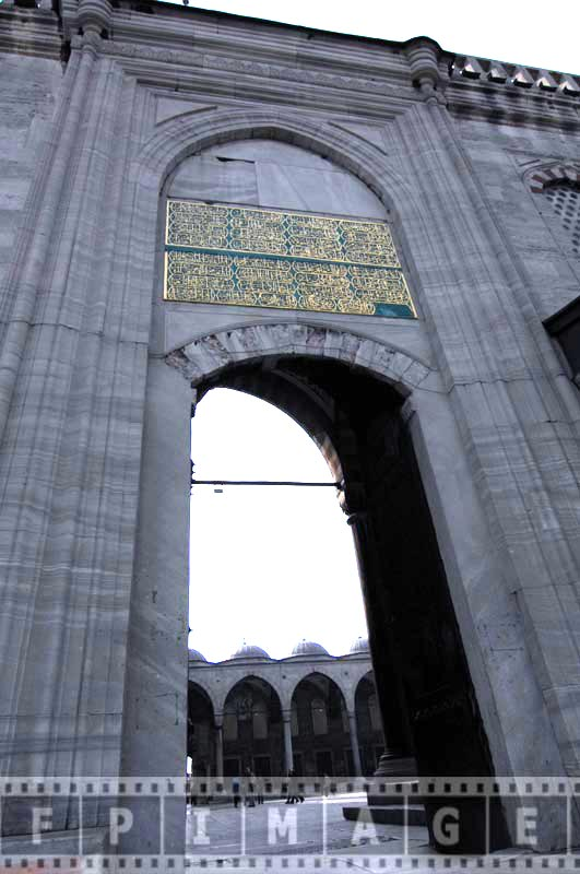 Golden calligraphy writing above the entrance - exterior decor of the mosque