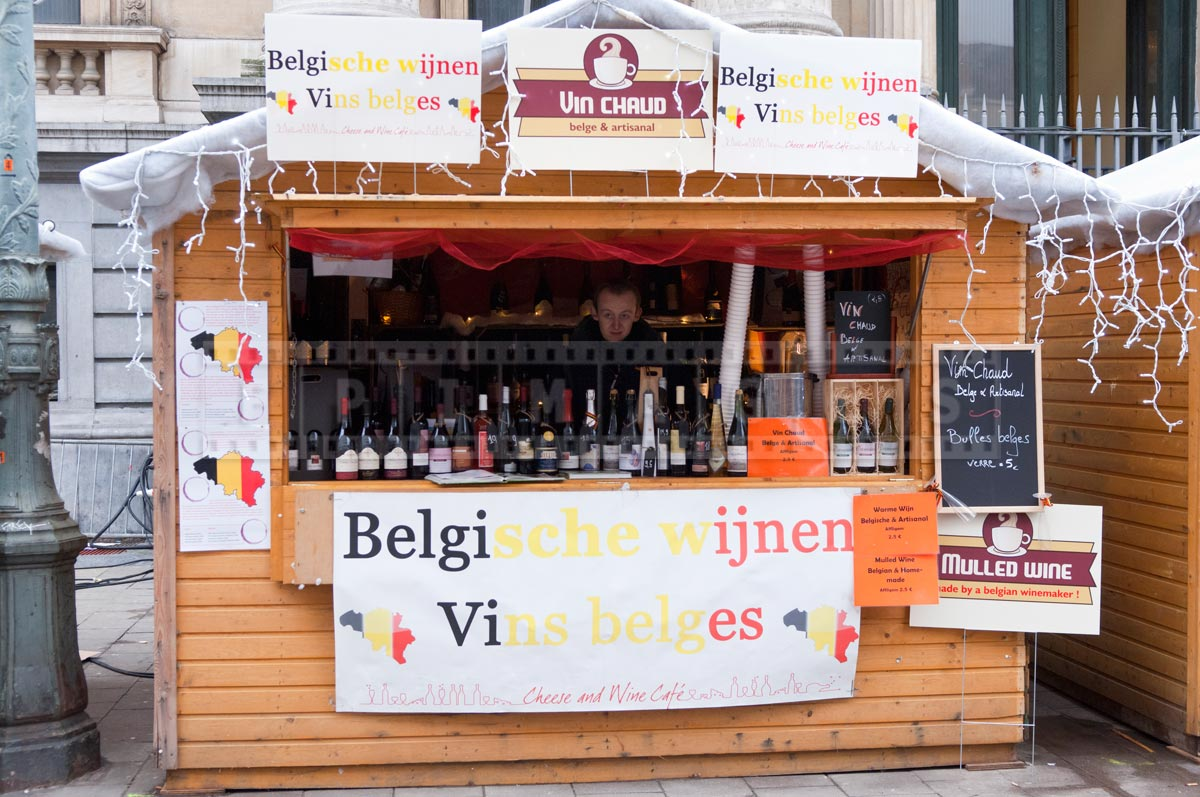 a wooden booth selling Belgian wines by the bottle and hot wine by the glass