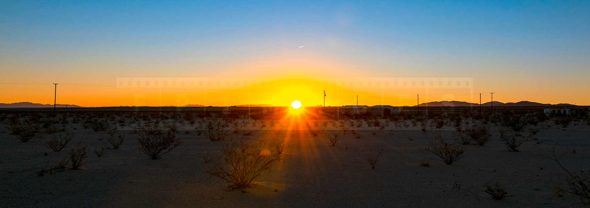 Sun rising above the horizon in the high desert of 29 Palms