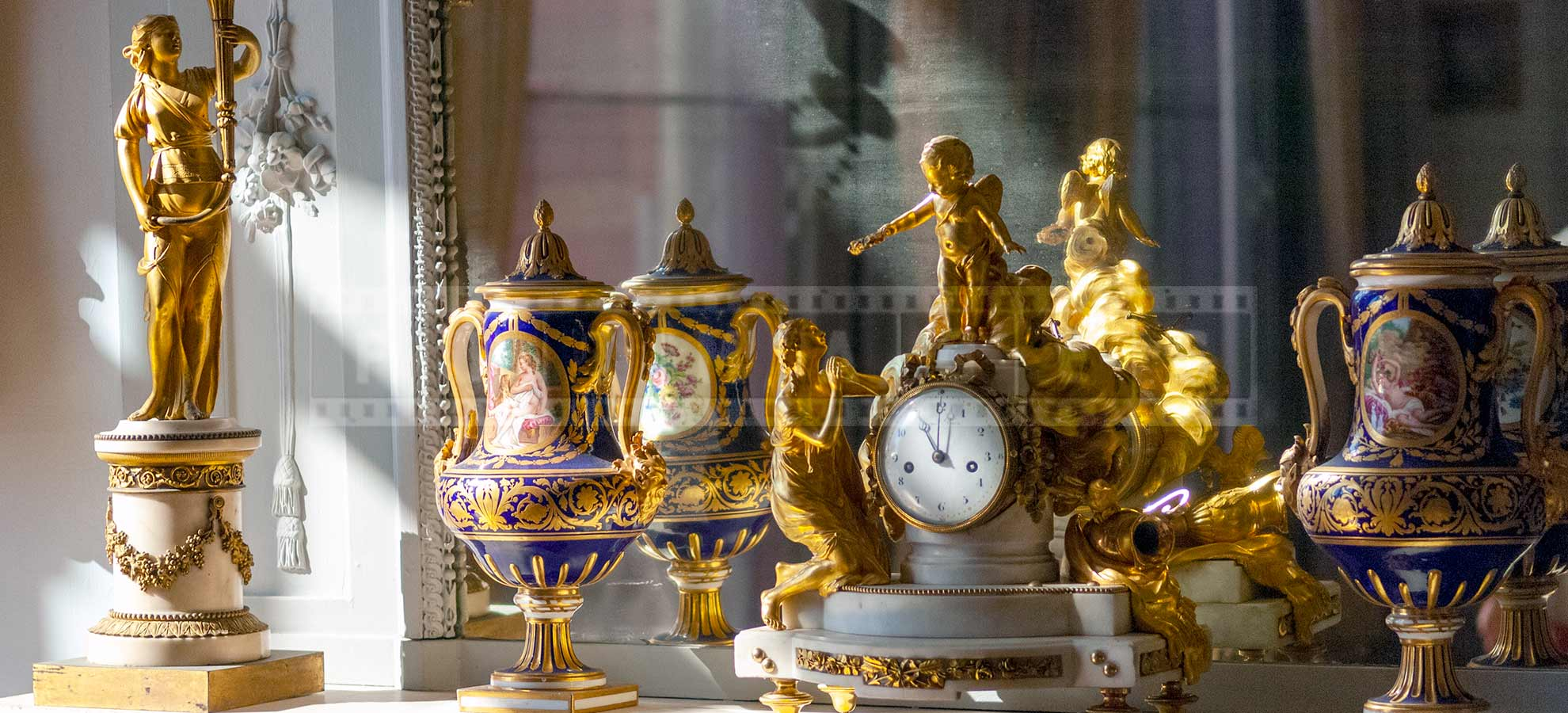 clock in front of a mirror surrounded by two vases