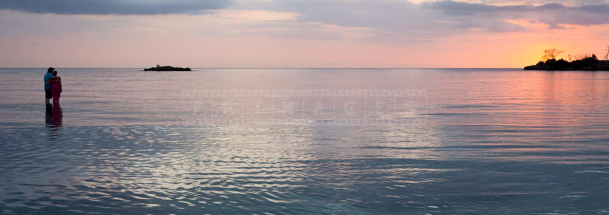Couple watching gorgeous sunset over the Caribbean sea in Negril Jamaica