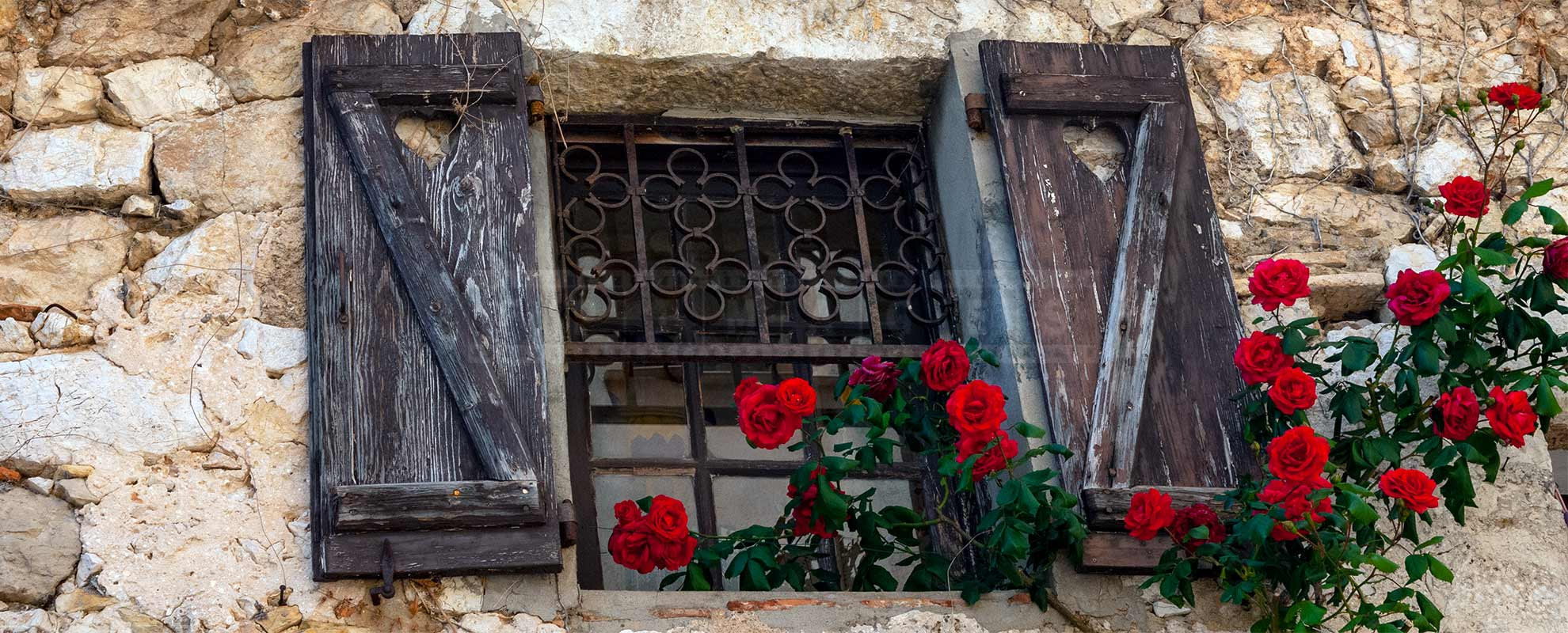 Beautiful medieval window with red roses in Eze Village